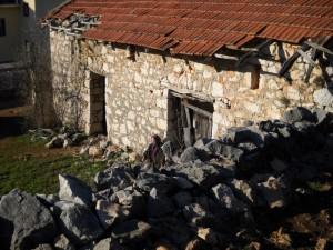 Una anciana reza el Rosario delante de su casa, en Medjugorje