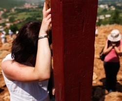 Una mujer en oración en la cruz de la Colina de las Apariciones de Medjugorje